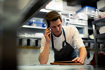 Young male chef reading digital tablet and talking on smartphone in kitchen - p429m2200740 by Sofie Delauw