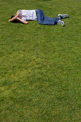 Child lying in the grass - p445m1040051 by Marie Docher
