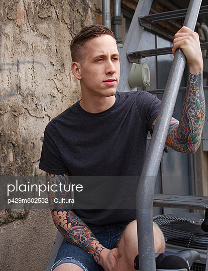 Young tattooed man looking away on staircase - p429m802532 by Cultura