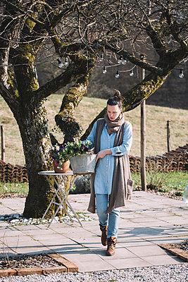 Woman carrying basket with fresh flowers - p300m2004263 von Alberto Bogo