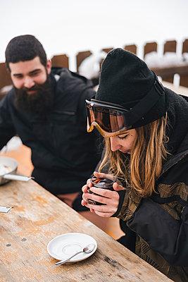 Couple in skiwear having a hot drink at mountain lodge - p300m2029401 von Juri Pozzi