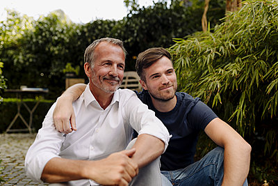 Smiling father and son looking away while sitting together in backyard - p300m2275054 by Gustafsson