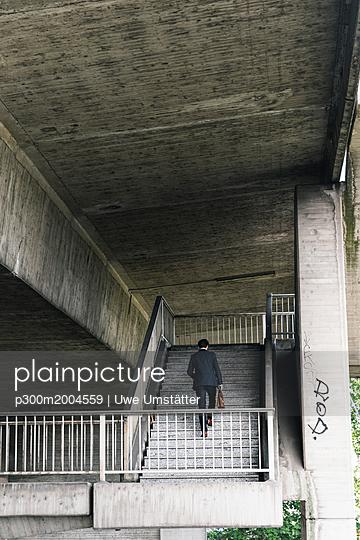 Businessman at underpass walking upstairs - p300m2004559 von Uwe Umstätter