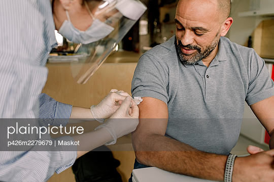Mature man looking at female healthcare worker injecting medicine - p426m2279679 by Maskot