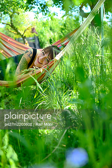Happy young woman in a hammock in the garden - p427m2203602 by Ralf Mohr