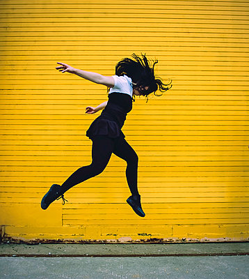 Side view of woman jumping against yellow shutter - p1166m1209713 by Cavan Images