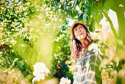 Frau im Garten staunt - p1312m1176977 von Axel Killian