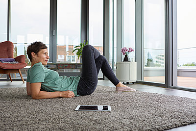 Woman lying on the floor at home with tablet looking out of balcony door - p300m2012976 von Rainer Berg