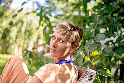 Portrait of woman relaxing in garden - p300m2154619 by Bernd Friedel