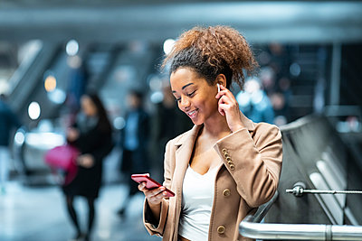 Smiling young woman with cell phone and earbuds at subway station - p300m2167645 by William Perugini