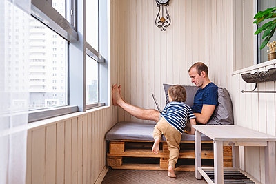 Boy looking at father using laptop on seat in home office - p300m2277706 by Katharina und Ekaterina