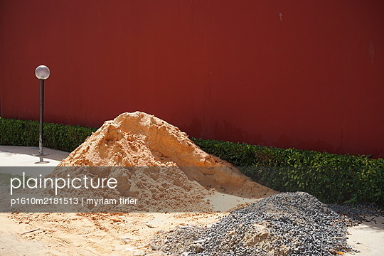 pile of orange sand with red wall behind - p1610m2181513 by myriam tirler
