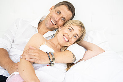 Happy couple lying on bed, portrait - p1640m2259615 by Holly & John