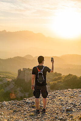 Spain, Barcelona, Natural Park of Sant Llorenc, man hiking and taking a picture of the view at sunset - p300m2058571 von VITTA GALLERY