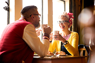 Quirky couple relaxing in bar and restaurant, Bournemouth, England - p429m1477719 by JAG IMAGES