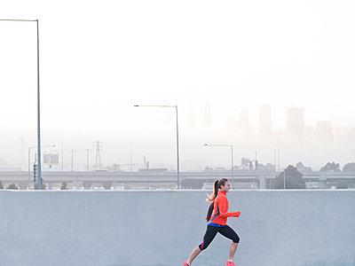 Female runner running in misty morning cityscape, Melbourne, Australia - p924m1468755 by Elke Meitzel
