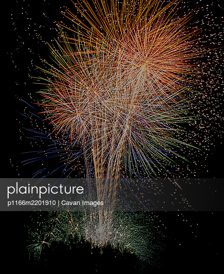 Several colorful fireworks exploding in the dark sky in the midd - p1166m2201910 by Cavan Images