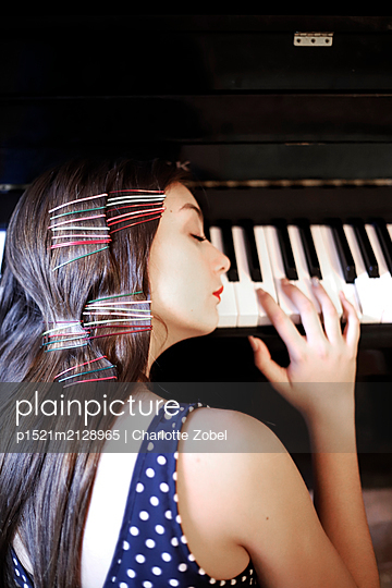 Young woman leaning against the piano - p1521m2128965 by Charlotte Zobel