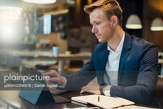 Businessman using digital tablet at table in cafe - p300m2206576 by Daniel Ingold