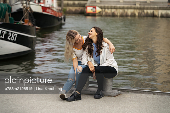 Girlfriends sitting on pier on the waterfront - p788m2128519 by Lisa Krechting