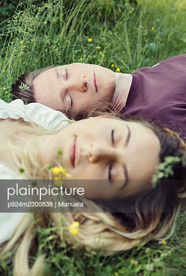 Austria, Vienna, Young couple with eyes closed lying on grass - p924m2300838 by Manuela