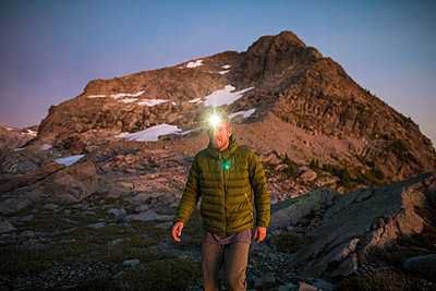 Mountaineer on the move, wearing headlamp at dusk in the mountains. - p1166m2095264 by Cavan Images