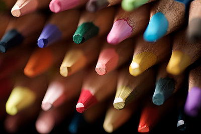 Watercolor pencils lined up on a black table. - p1166m2095611 by Cavan Images