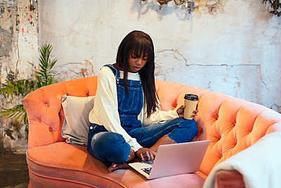 Young woman sitting on the couch with coffee to go in a loft using laptop - p300m1581062 by Bonninstudio