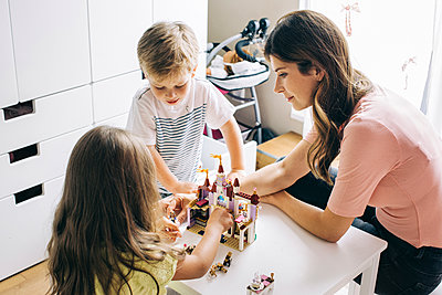 Mother with two children building up toy castle at home - p300m2029492 by Visualspectrum