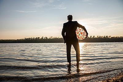 Back view of businessman with beach ball standing at lakeshore watching sunset - p300m2041832 von Jo Kirchherr