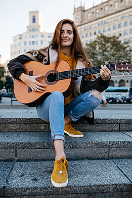 Red-haired woman playing the guitar in the city - p300m2058953 by Josep Rovirosa