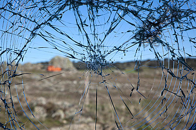 A blurred rural landscape seen through a shattered window - p301m799870f by Oliver Steinberger