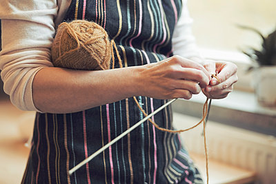 Midsection of woman knitting at home - p426m958691f by Maskot