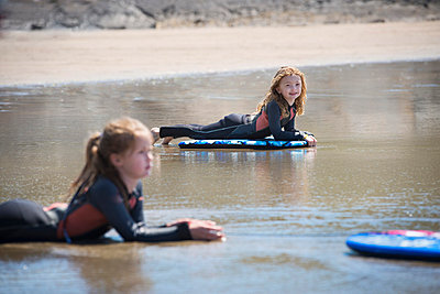 Children on surfboards in water - p429m696640 by Zac Macaulay