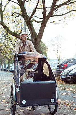 Man carrying his dog with a bike - p432m949444 by mia takahara