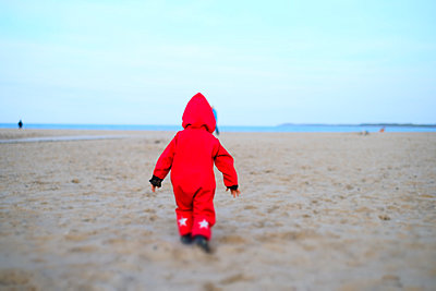 Child in red snowsuit on the beach - p858m2150494 by Lucja Romanowska