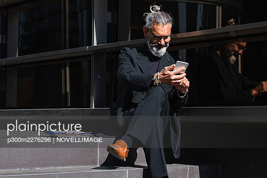 Male entrepreneur working on mobile phone while sitting on steps by building - p300m2276296 by NOVELLIMAGE