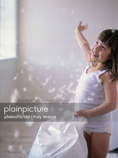 Girl playing with feathers from split pillowcase (Model Released) - p349m2167653 by Polly Wreford