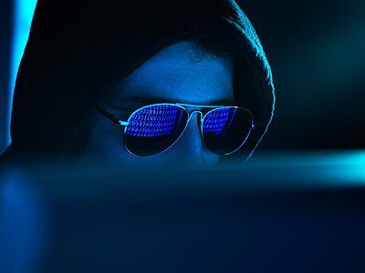 Cyber Crime, reflection in spectacles of virus hacking a computer, close up of face - p300m2102463 von Andrew Brookes
