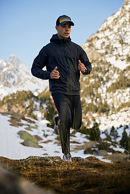 Young male athlete running on mountain in winter - p300m2250035 by Aitor Carrera Porté