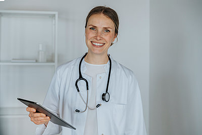 Smiling doctor holding digital tablet - p300m2286369 by Mareen Fischinger