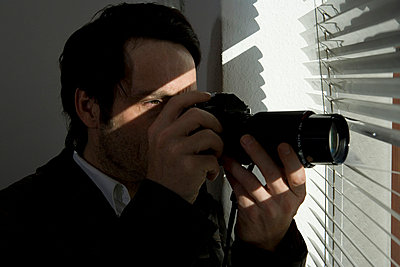 A man looking through blinds with a camera - p3017851f by Marco Baass