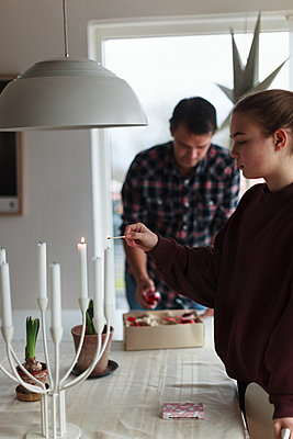 Girl lighting candles - p312m1558383 by Christina Strehlow