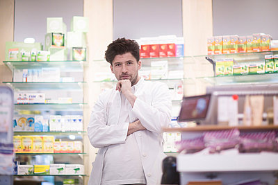 Portrait of young male pharmacist with hand on chin in pharmacy - p429m1547911 by Sigrid Gombert