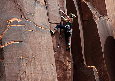 A rock climber tackles an overhanging crack in a sandstone wall on the cliffs of Indian Creek - p8713159 by David Pickford