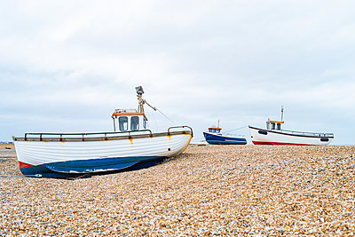 Fishing boats on the shingle beach waiting to go back out to the water, Dungeness, Kent, England, United Kingdom - p871m2113691 by Paul Porter