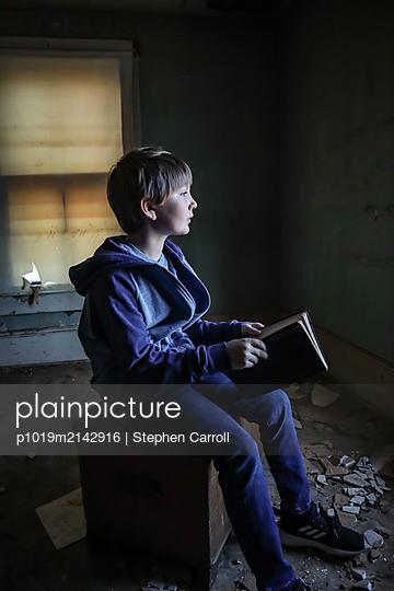 Junge mit Buch in altem Haus - p1019m2142916 von Stephen Carroll