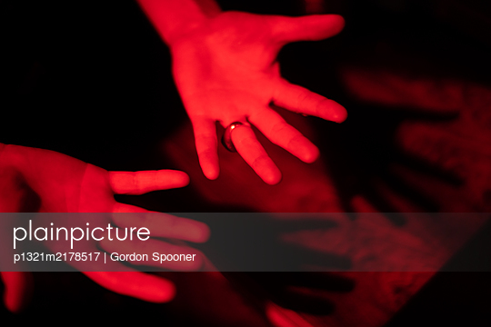 Hands of a woman in red light - p1321m2178517 by Gordon Spooner