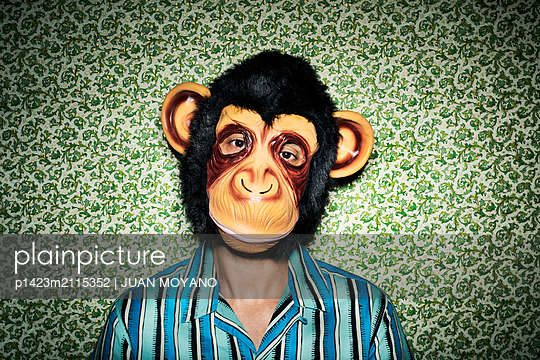 Man with a monkey mask against a wallpapered wall - p1423m2115352 by JUAN MOYANO