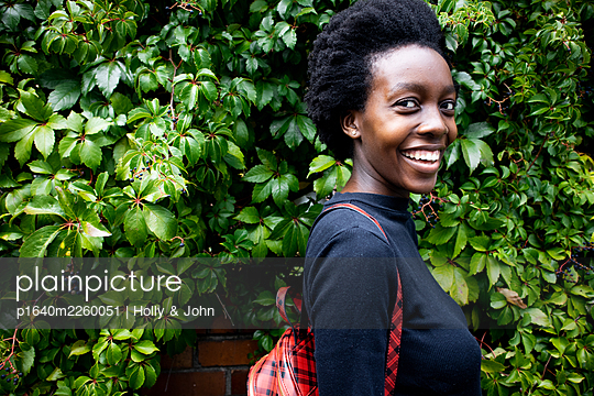 African woman with backpack, portrait - p1640m2260051 by Holly & John
